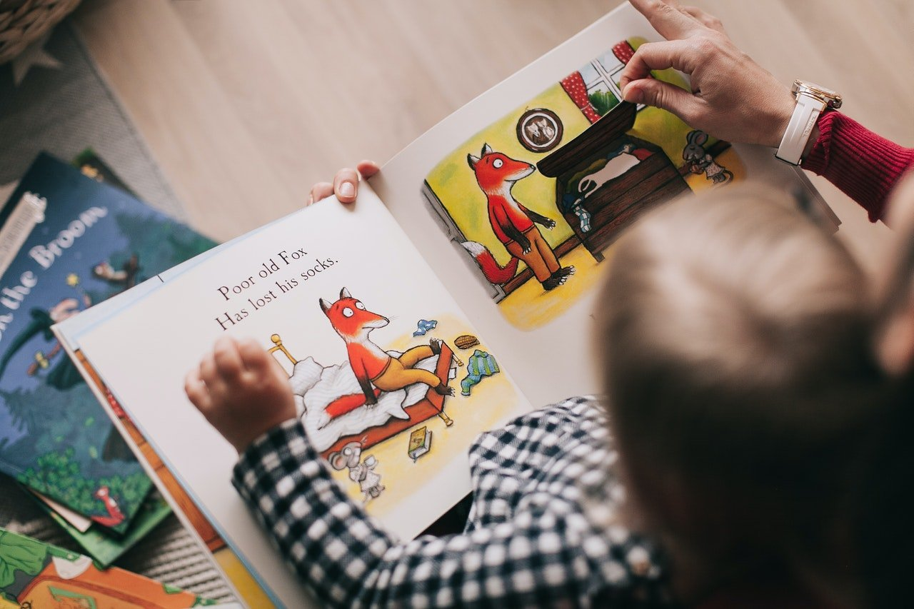 A young child reading a book | Photo: Pexels