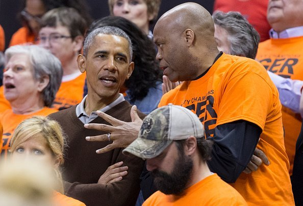 Barack Obama (L) sits beside his brother-in-law Craig Robinson while attending the Green Bay versus Princeton women's college basketball game in the first round of the NCAA tournament, March 21, 2015, in College Park, Maryland. | Source: Getty Images.