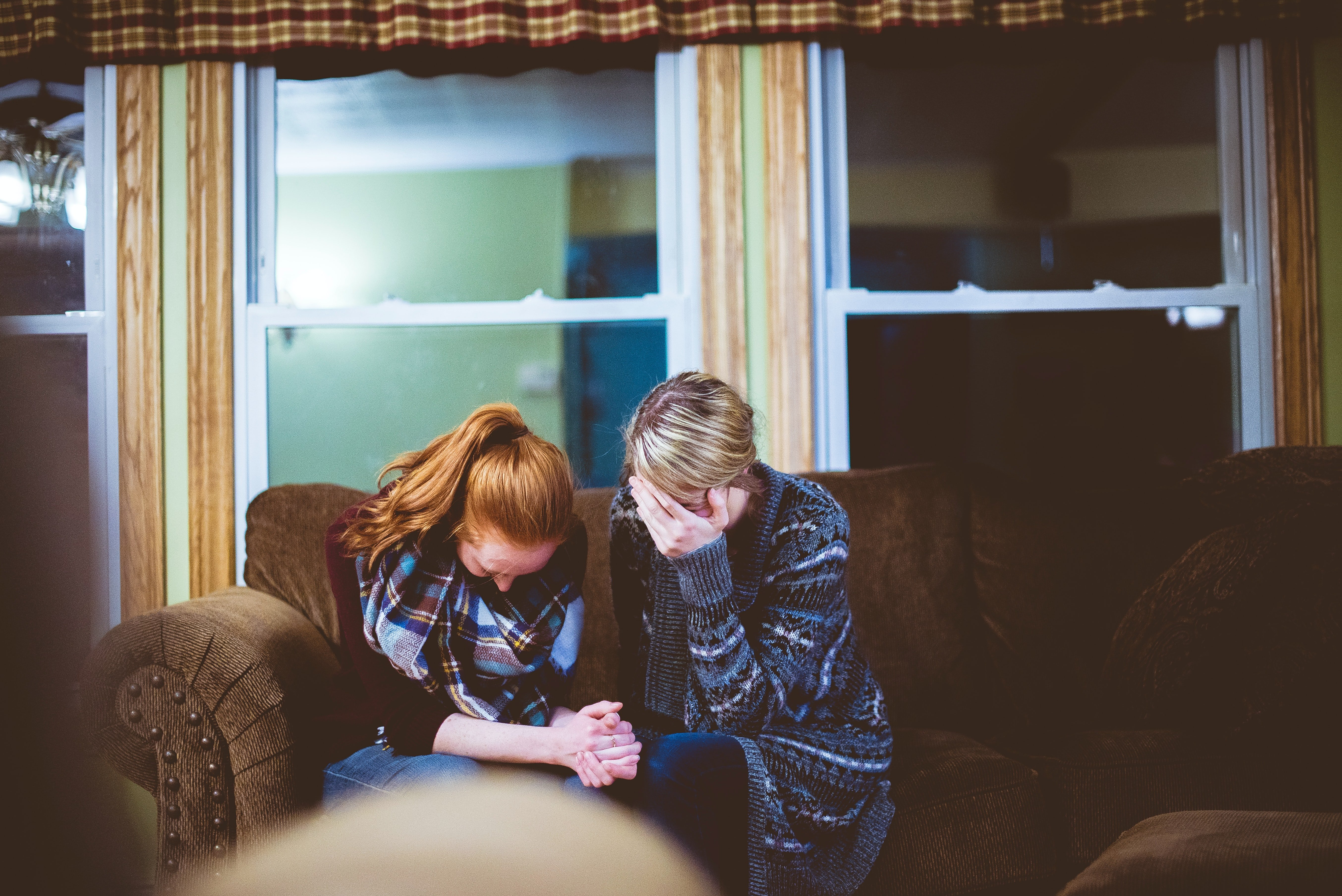 Distressed women sitting on a couch | Photo: Unsplash