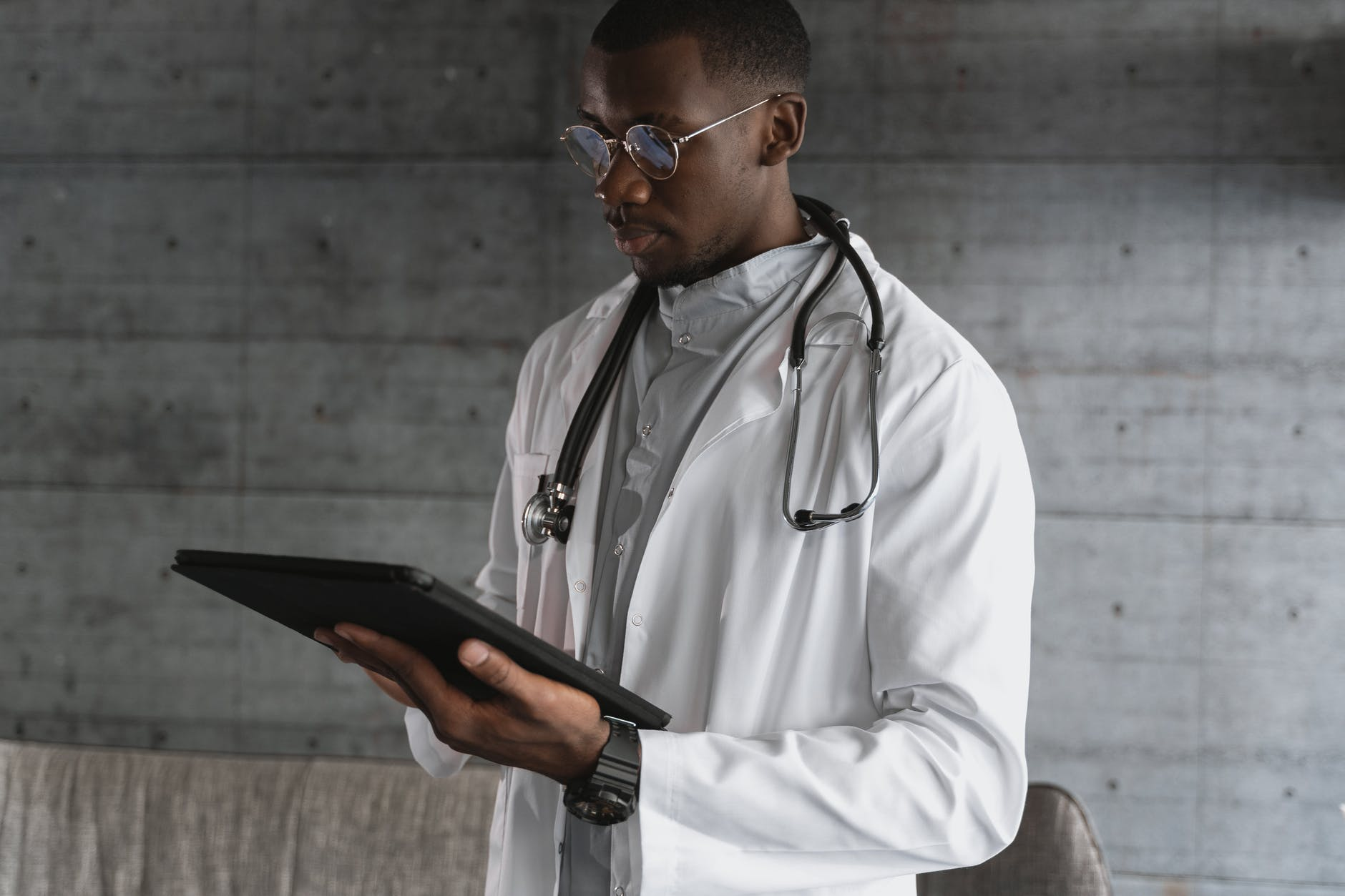 A doctor holding the black tablet.   Photo: Pexels