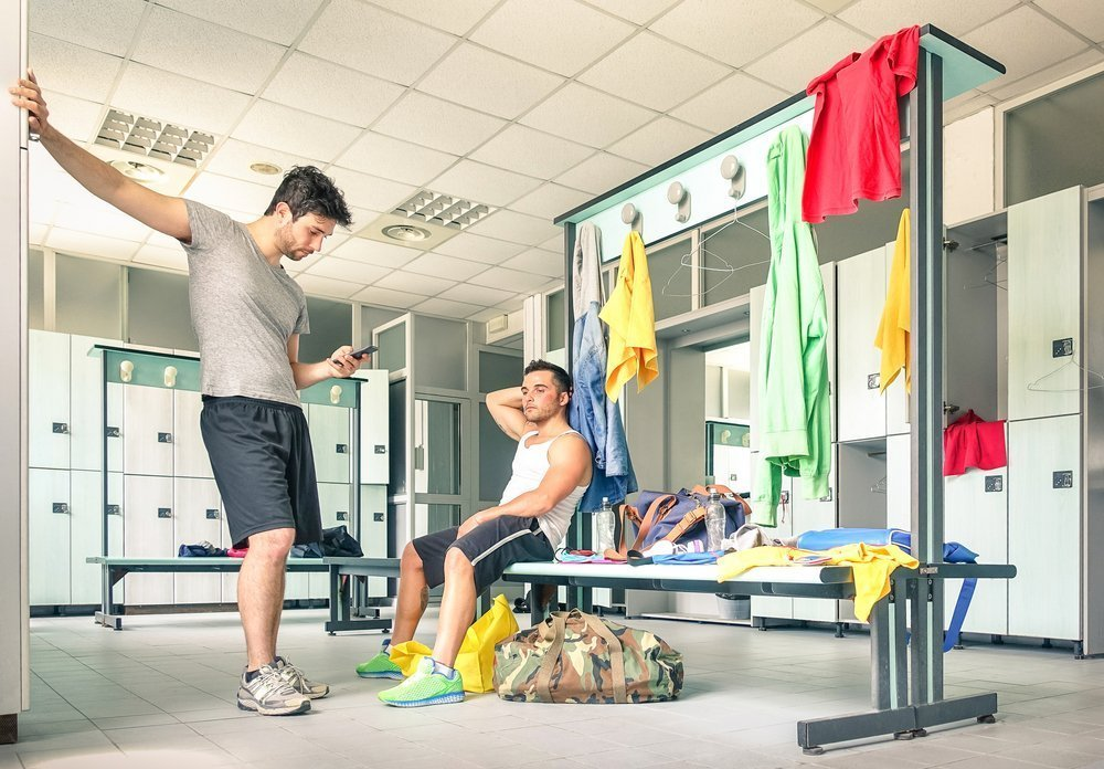 Man with mobile phone in locker room | Image: Shutterstock