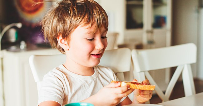 A child holding a slice of bread on the table. | Source: Shutterstock