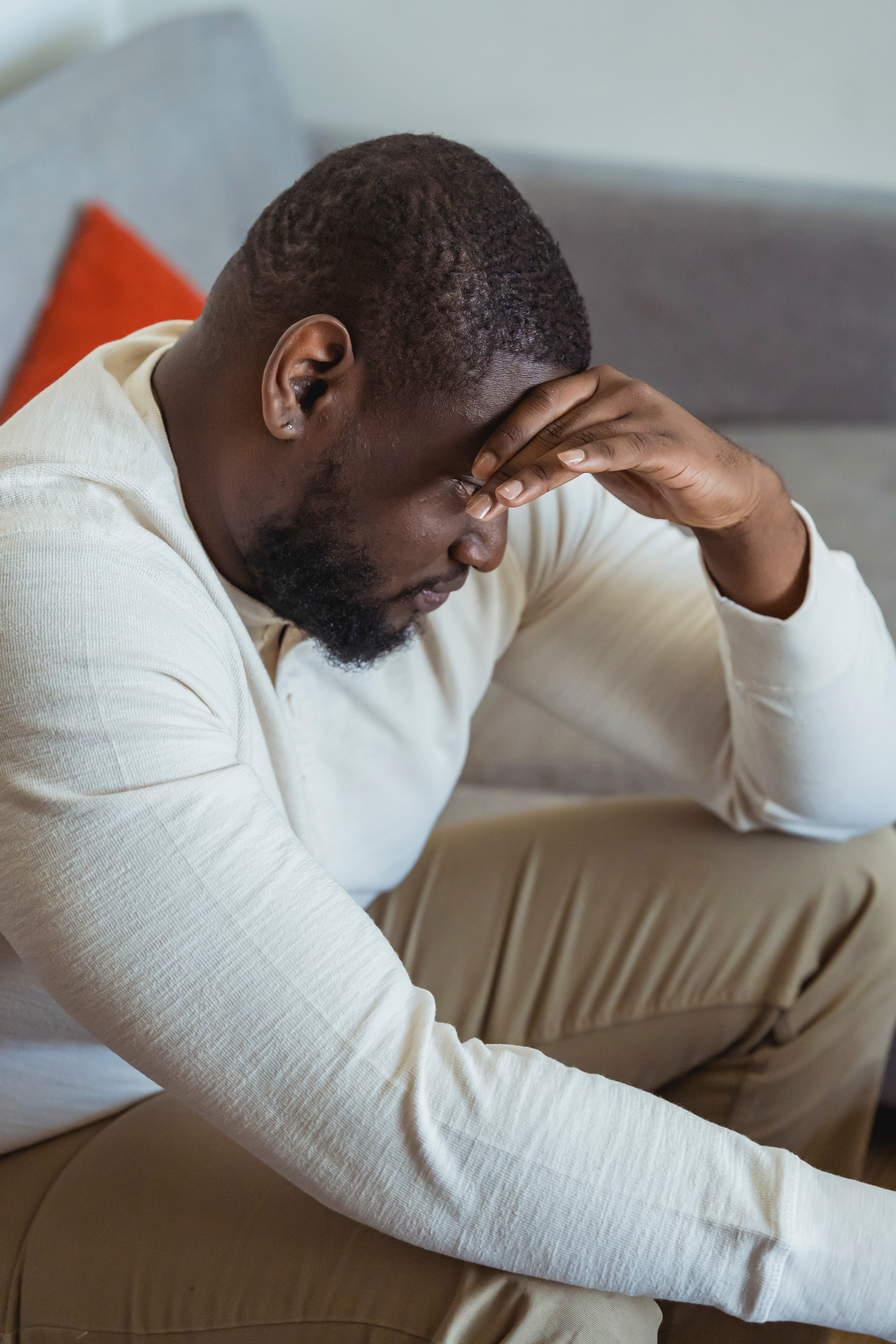 Pensive man sitting on a sofa with his head bowed down and his hand on his forehead   Photo: Pexels