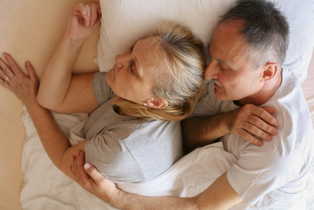 Elderly couple laying together | Shutterstock