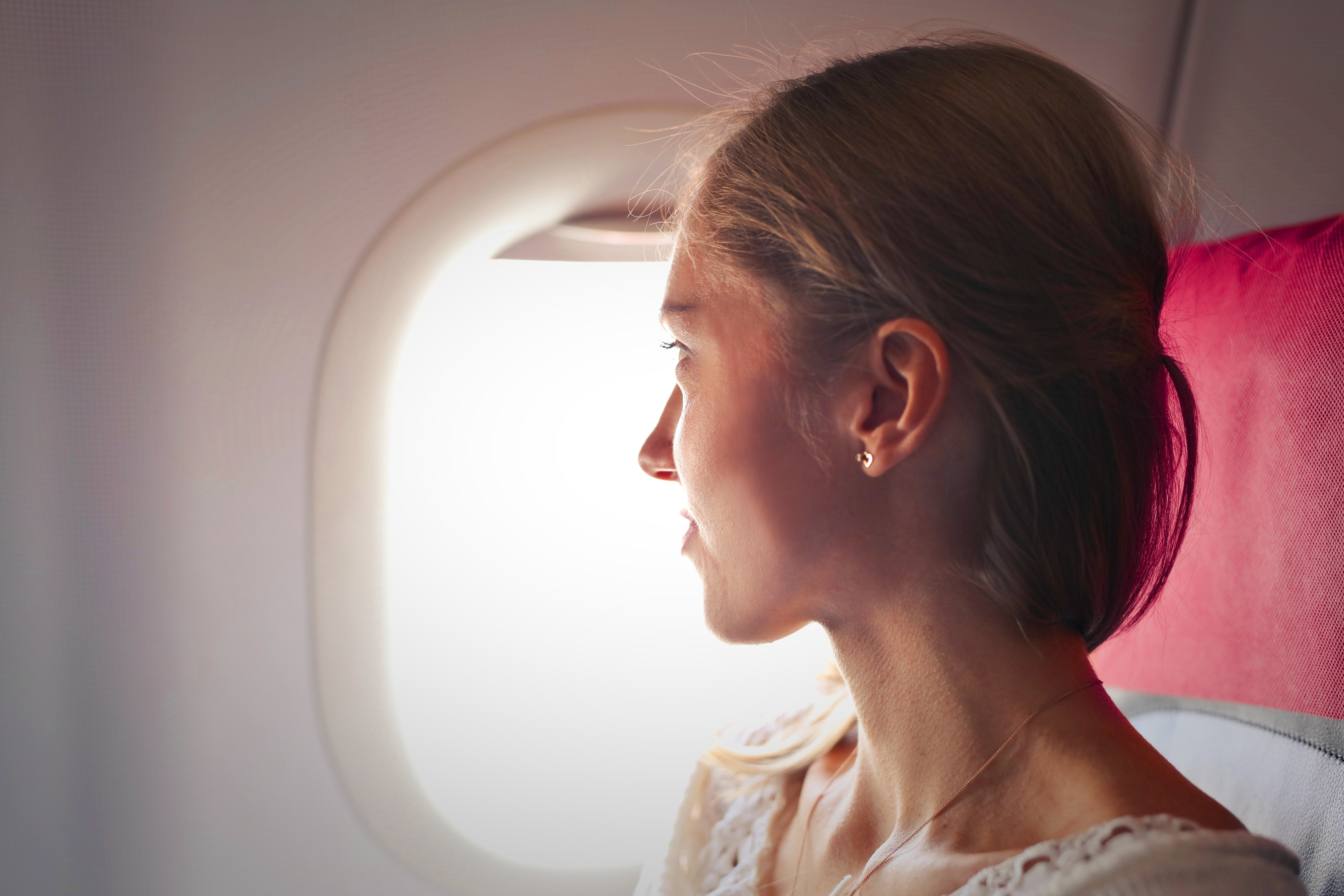 Woman looking through the window in the plane | Source: Pexels