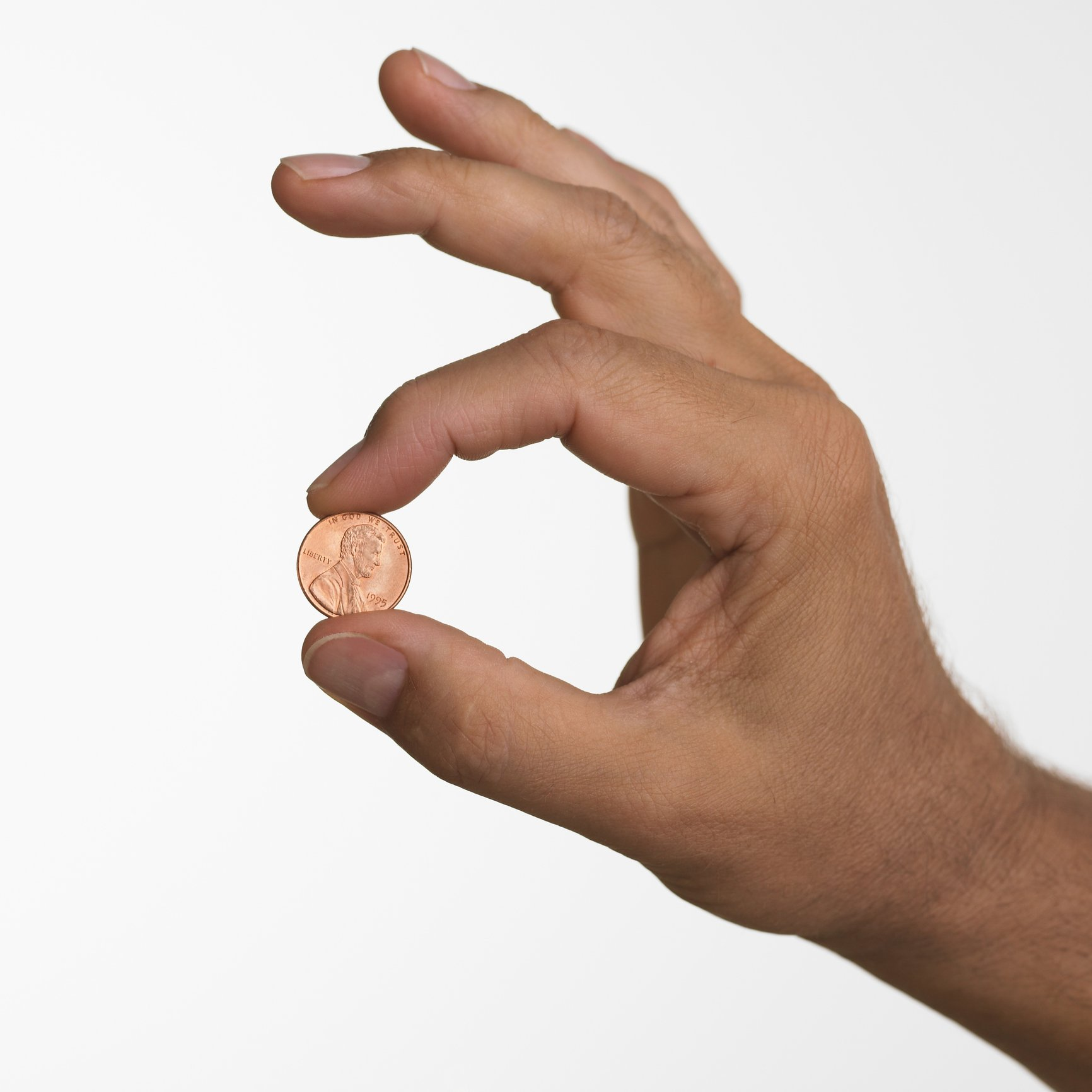Close up studio shot of man holding penny | Photo: Getty Images
