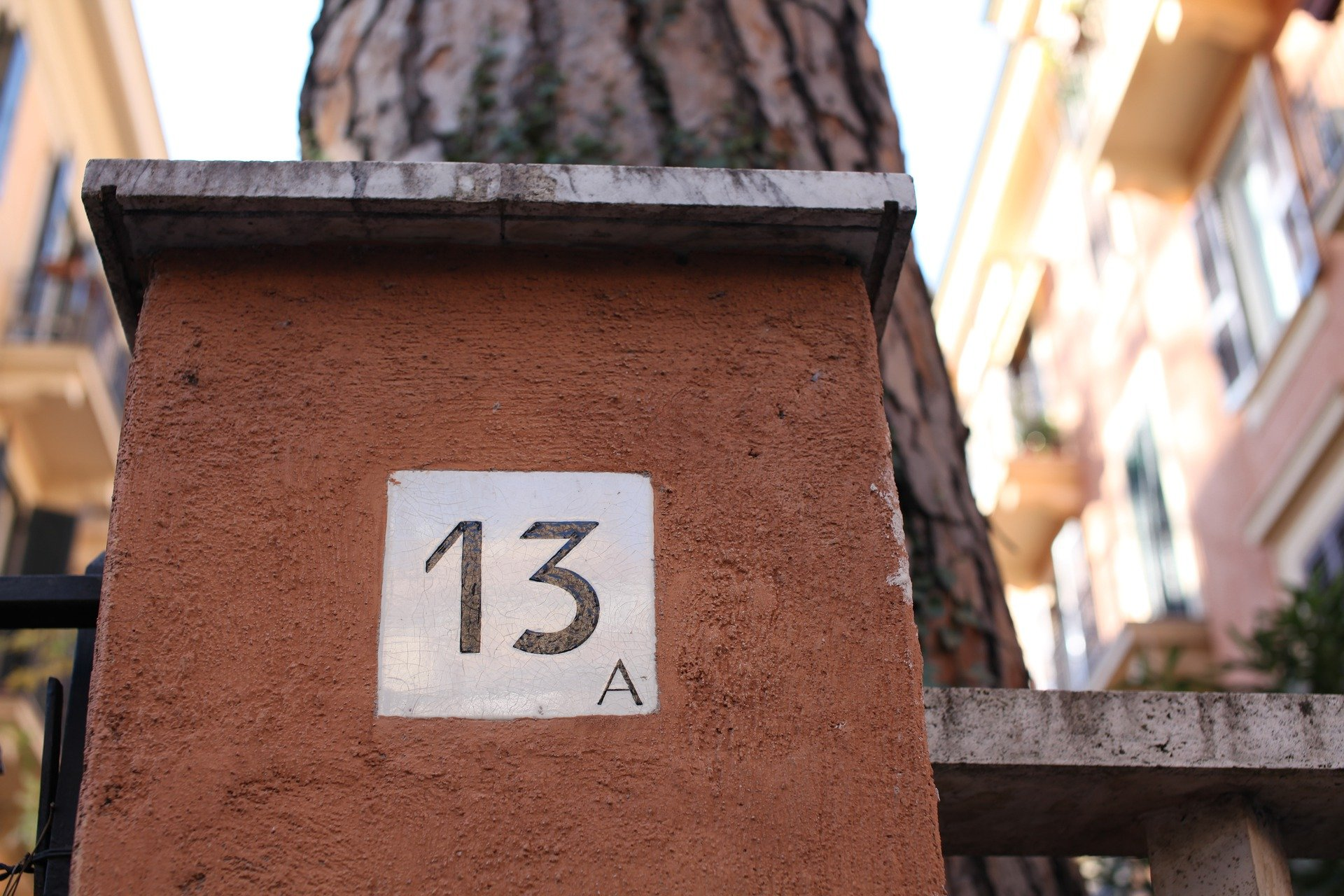 Gate No. 13 Against the Backdrop of a Tree & Buildings   Photo: Pixabay/thinkthanks
