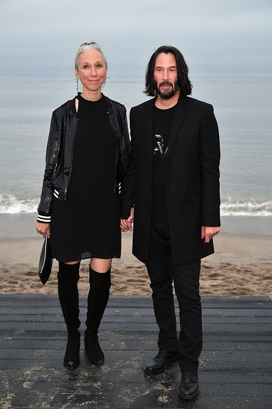 Alexandra Grant and Keanu Reeves attends the Saint Laurent Mens Spring Summer 20 Show in Paradise Cove Malibu, California. | Photo: Getty Images