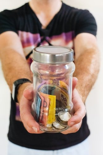A photo of a man holding a jar and asking for money. | Photo: Unsplash