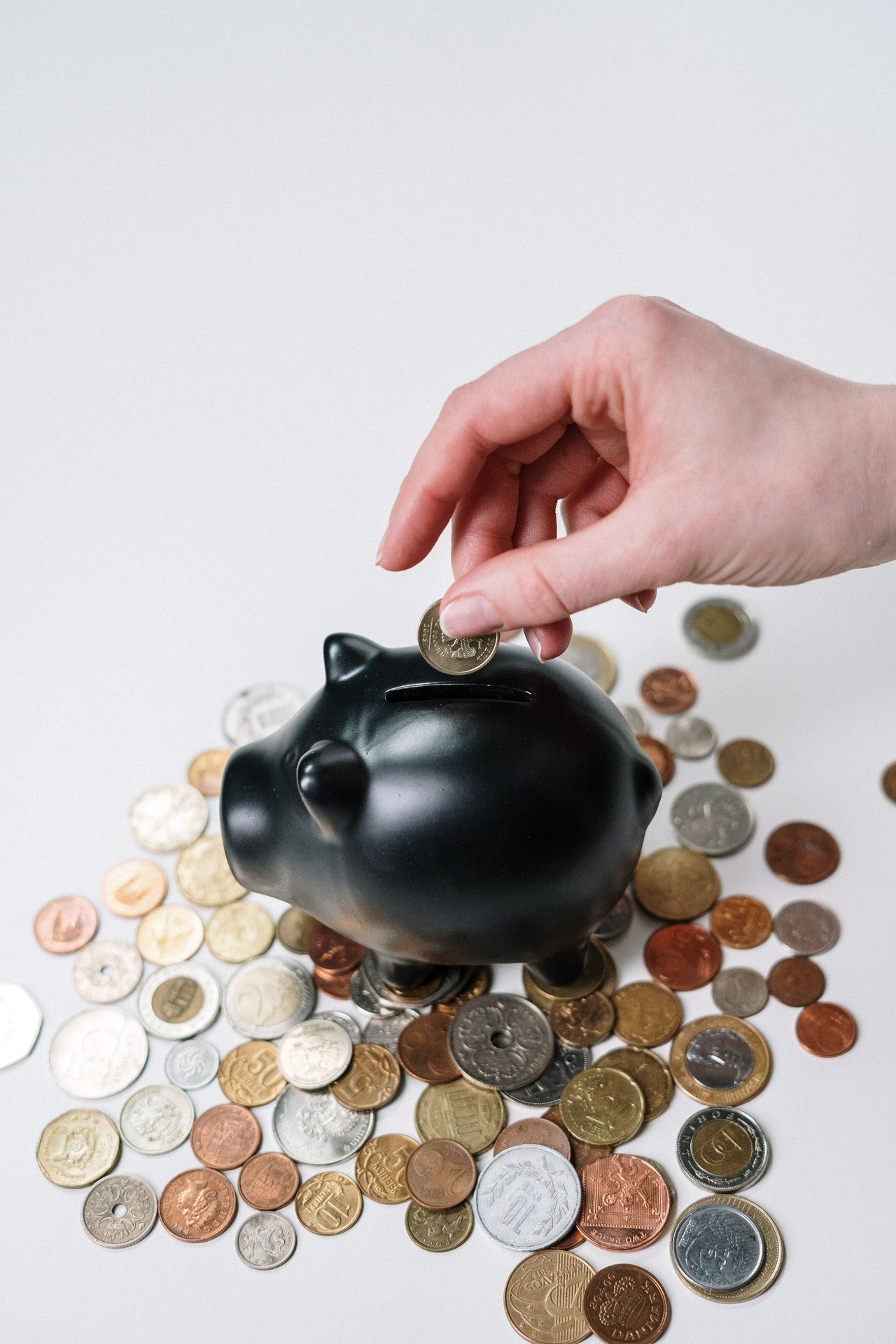 Person putting coin inside piggy bank   Source: Pexels