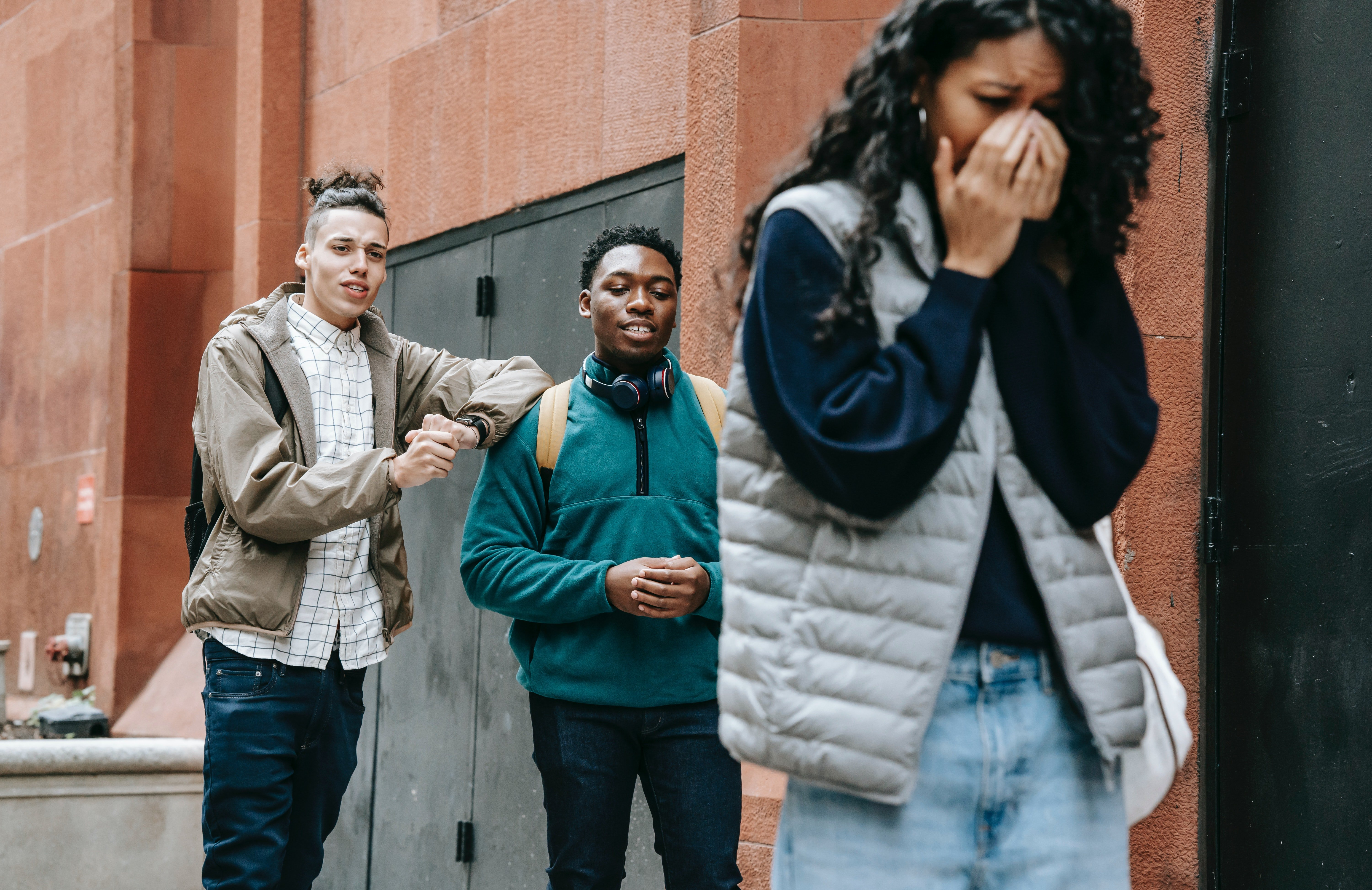 Young men bullying a crying lady   Photo: Pexels