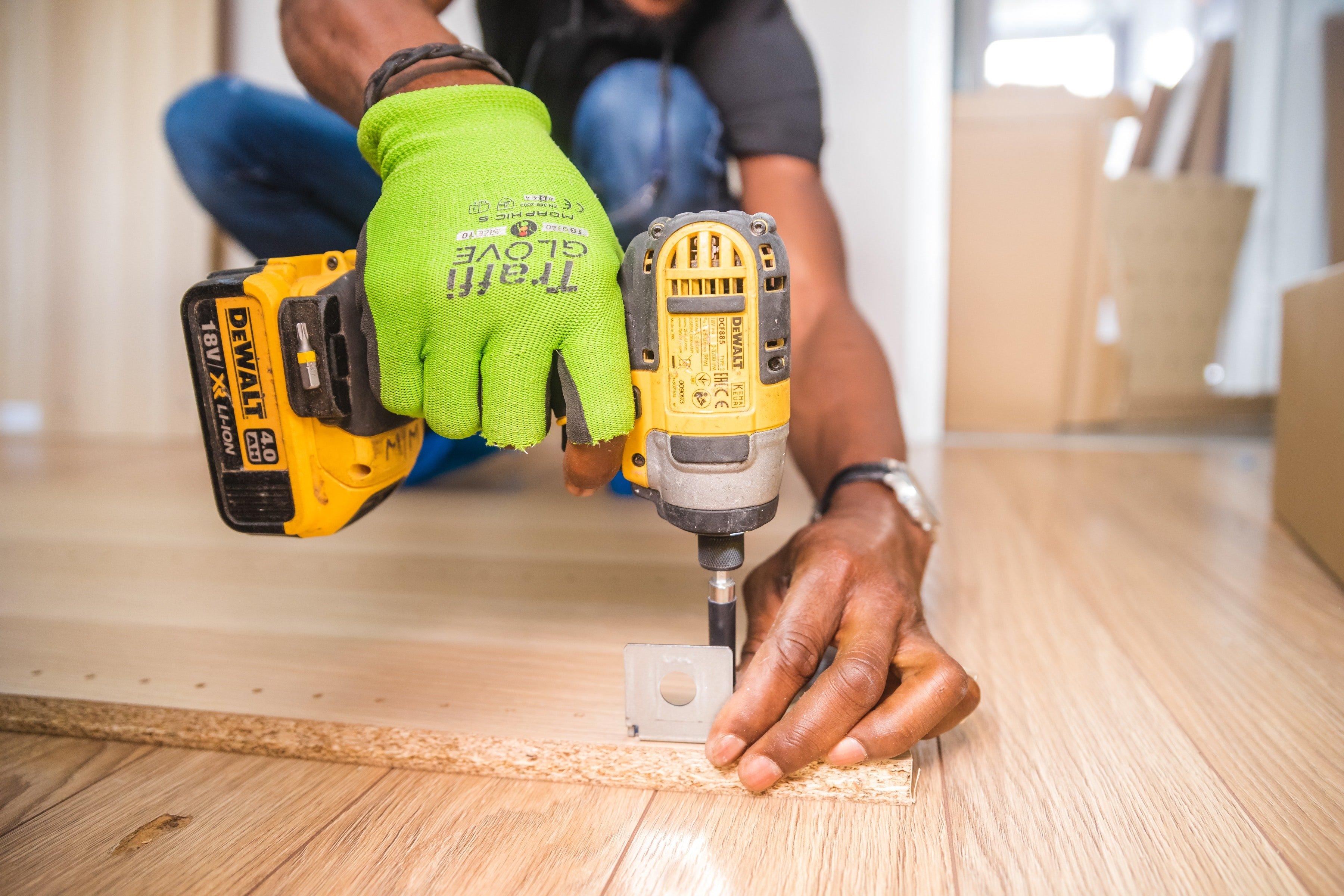 A handyman drilling into a piece of wood. | Photo: Pexels