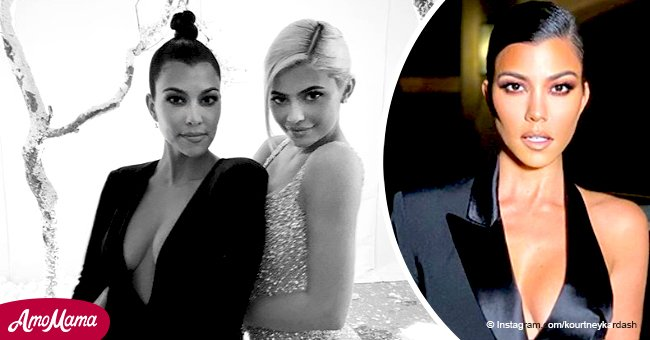 Kourtney Kardashian flaunts her breasts in a plunging mini dress after a 'tiny sister fight'