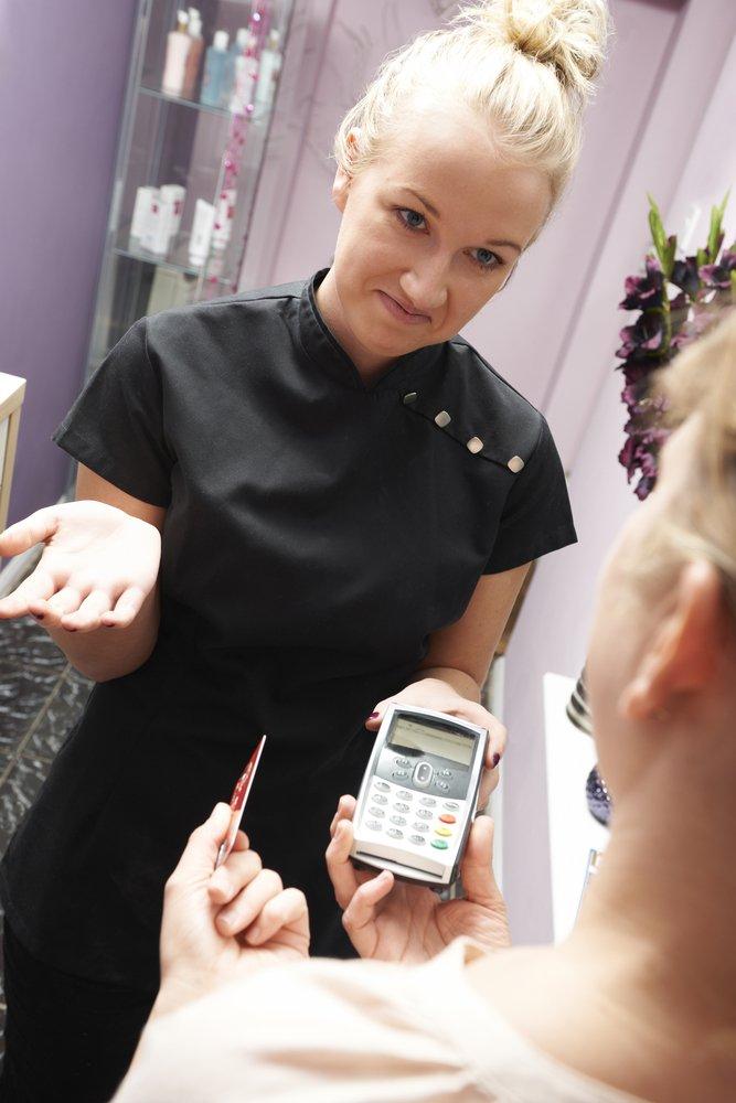 Une assistante commerciale explique qu'une carte de crédit a été refusée. | Shutterstock