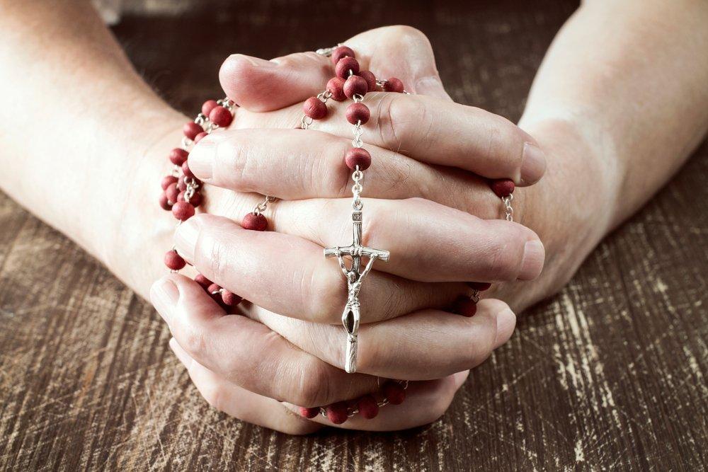 Persona rezando con un rosario en sus manos.| Fuente: Shutterstock