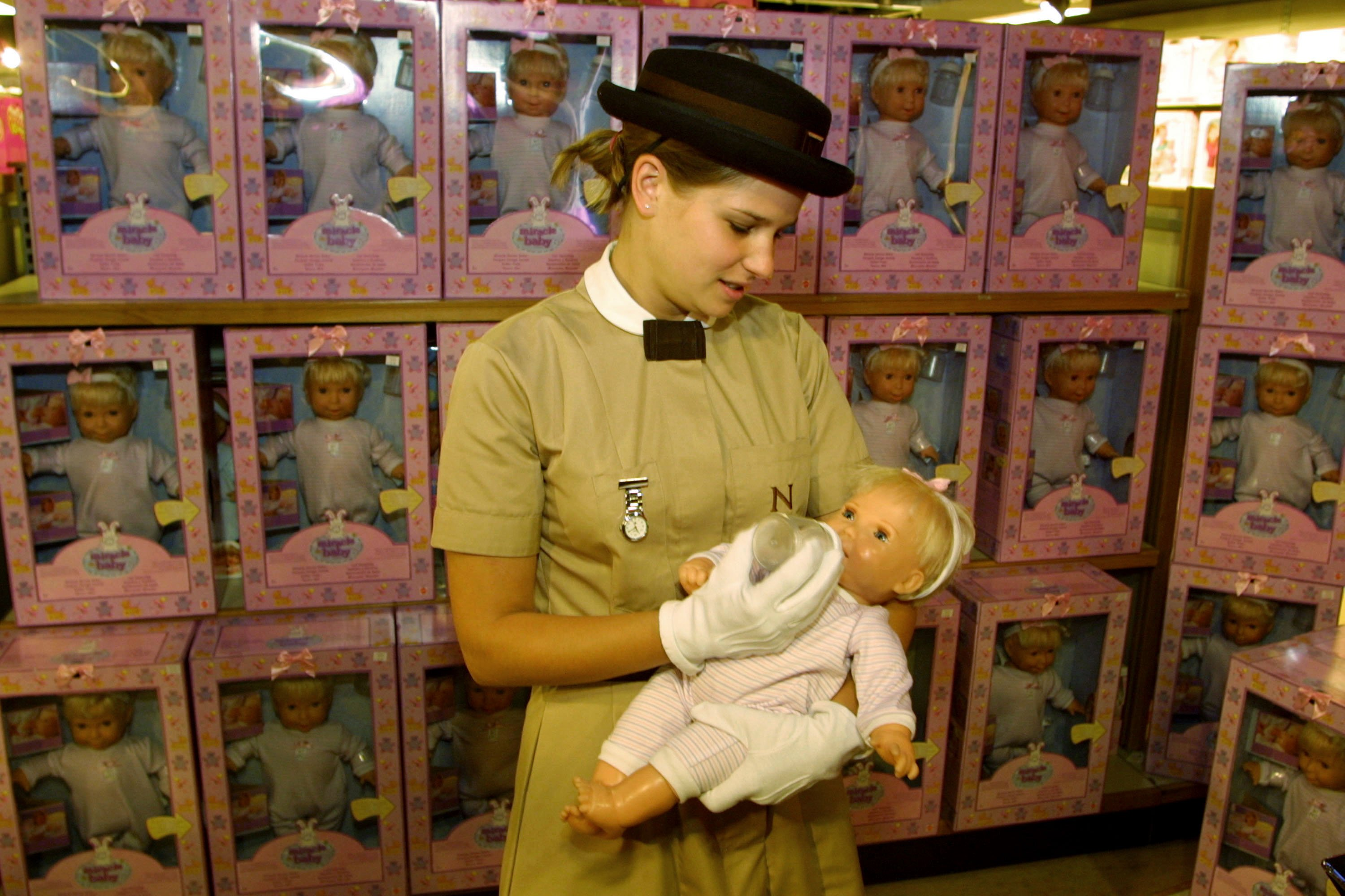 "Anna-Louise Kemp, a nanny from the Norland Nanny College, tries out the new ""Miracle Baby"" doll August 1, 2001 at the doll''s launch in London. The doll contains a microchip that simulates the behavior of a 6-month-old baby. 