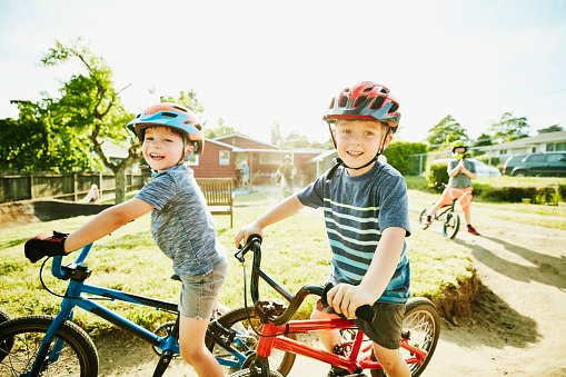 Photo of young boys preparing to ride BMX bikes on dirt track in backyard | Photo: Getty Images