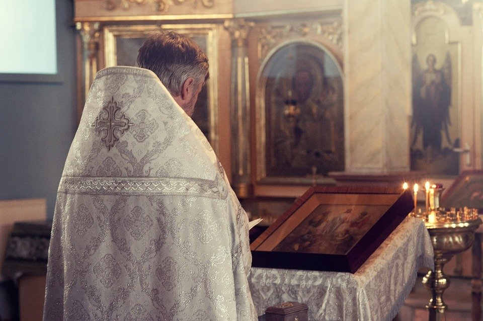 A Priest faces the altar while reading from a book in a Church   Photo: Pixabay