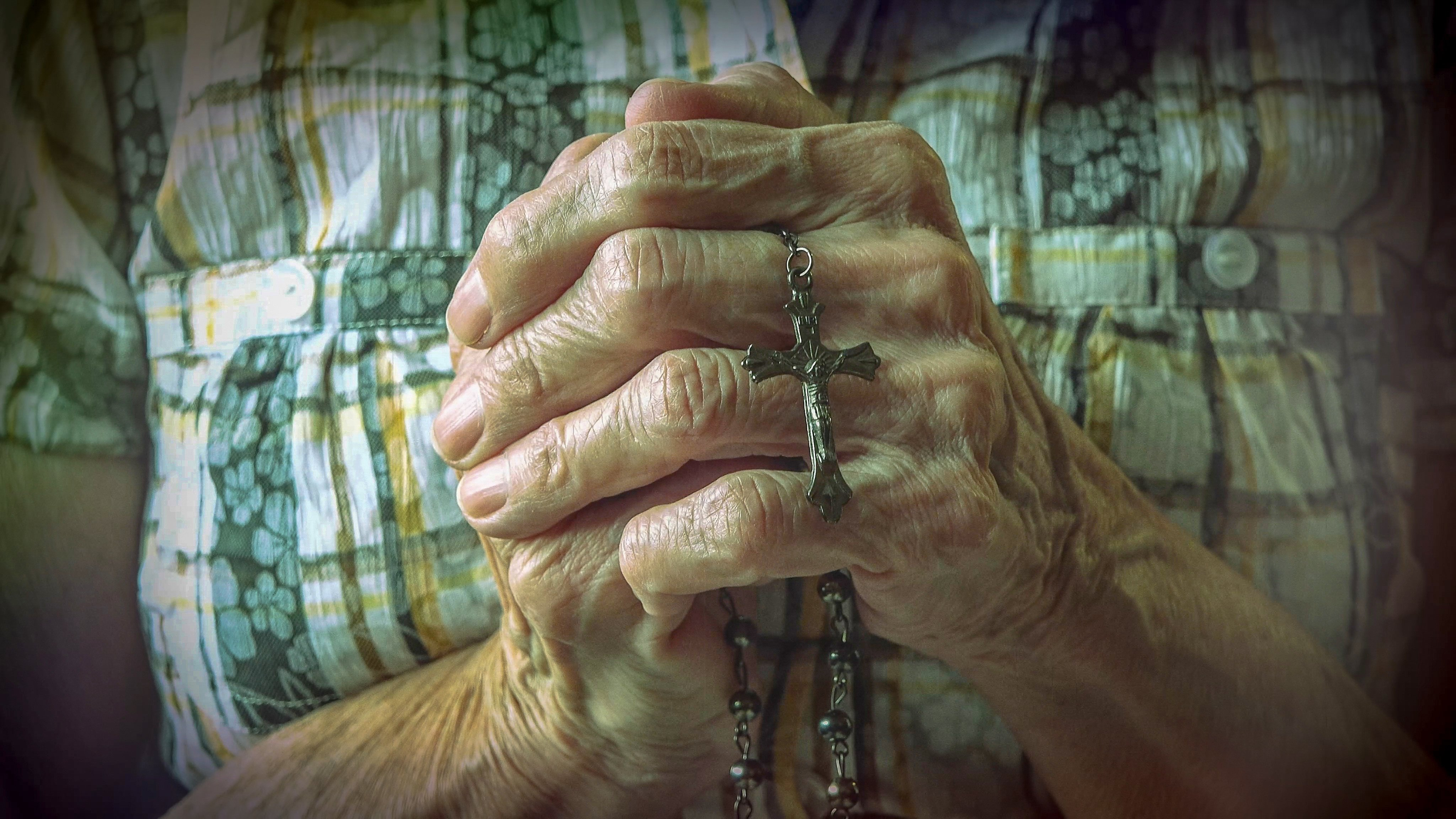 Elderly woman's hands holding a necklace with a cross | Photo: Shutterstock