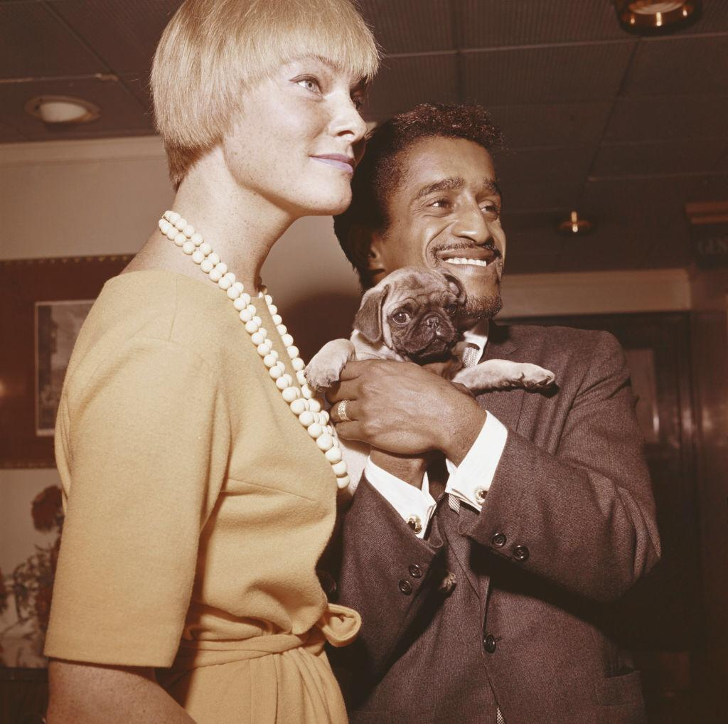 American singer, actor and comedian Sammy Davis Jr (1925-1990) pictured holding a Pug dog with his wife, Swedish actress May Britt in England in 1961 | Photo: Getty Images