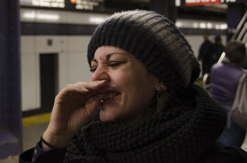 A woman laughing on the subway. | Photo: Flickr
