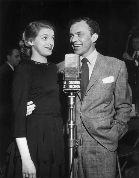 Rosemary Clooney and Frank Sinatra stand together in front of a Columbia Records microphone in this 1950 photo. | Source: Getty Images.