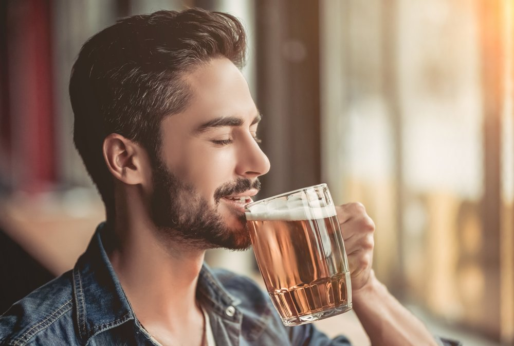 A young man drinking beer in the pub. | Photo: Shutterstock.