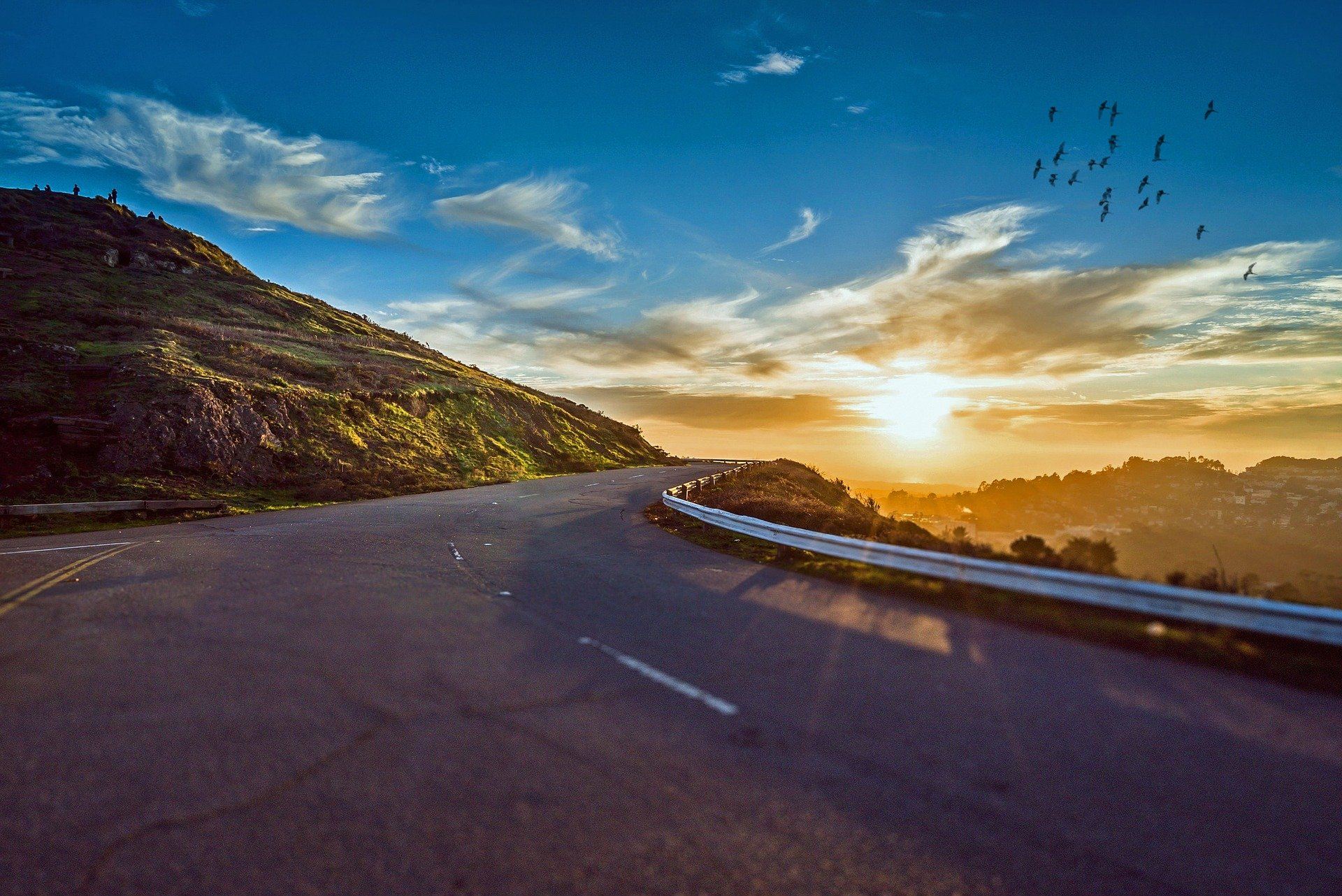 Picture of a winding road taken at sunrise.   Source: Pixabay.