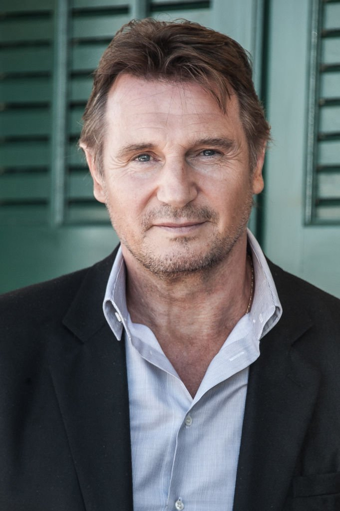 Liam Neeson next to the beach closet dedicated to him on the Promenade des Planches | Source: Getty Images