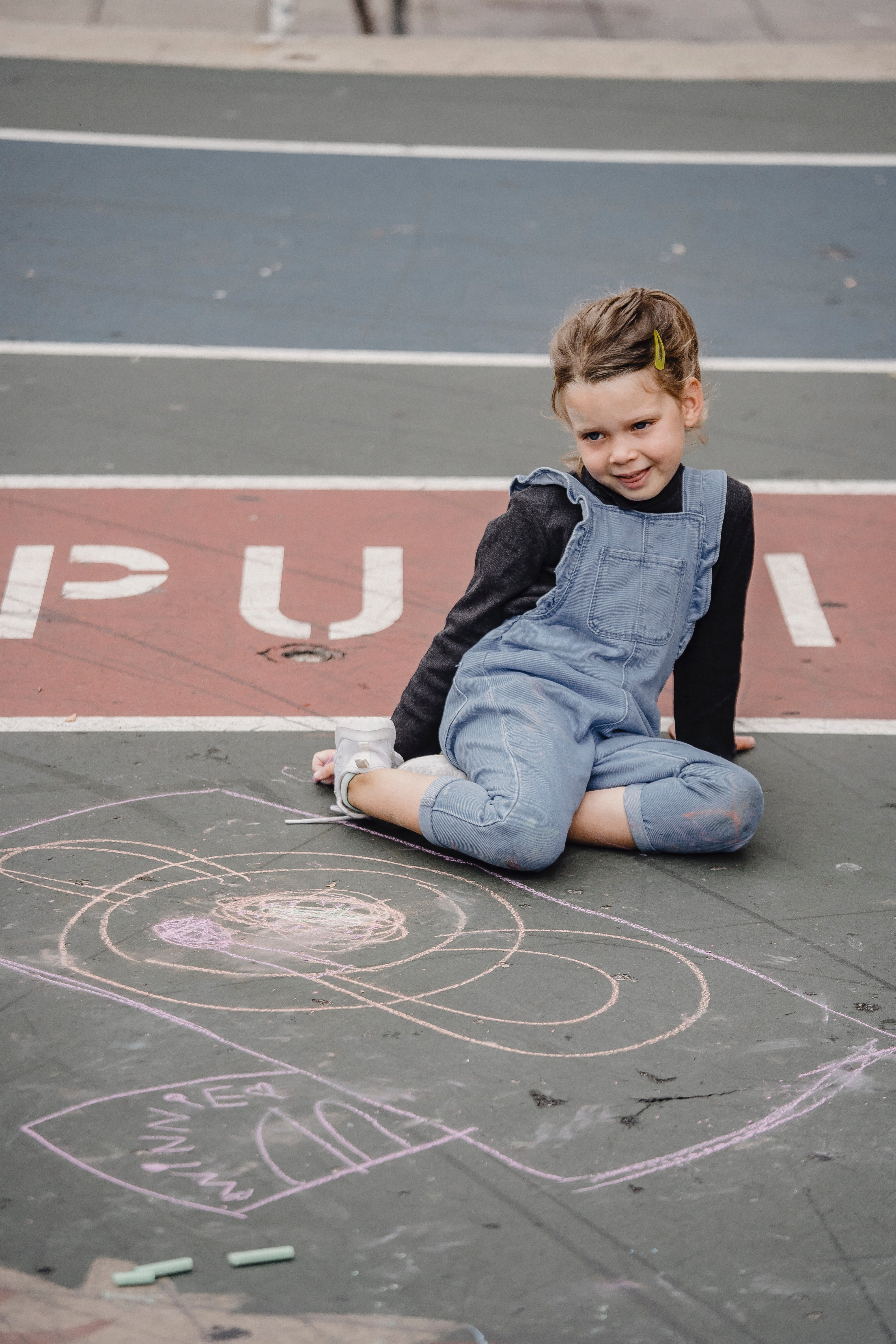 Pictured - A young girl sitting on asphalt neat chalk painting | Source: Pexels