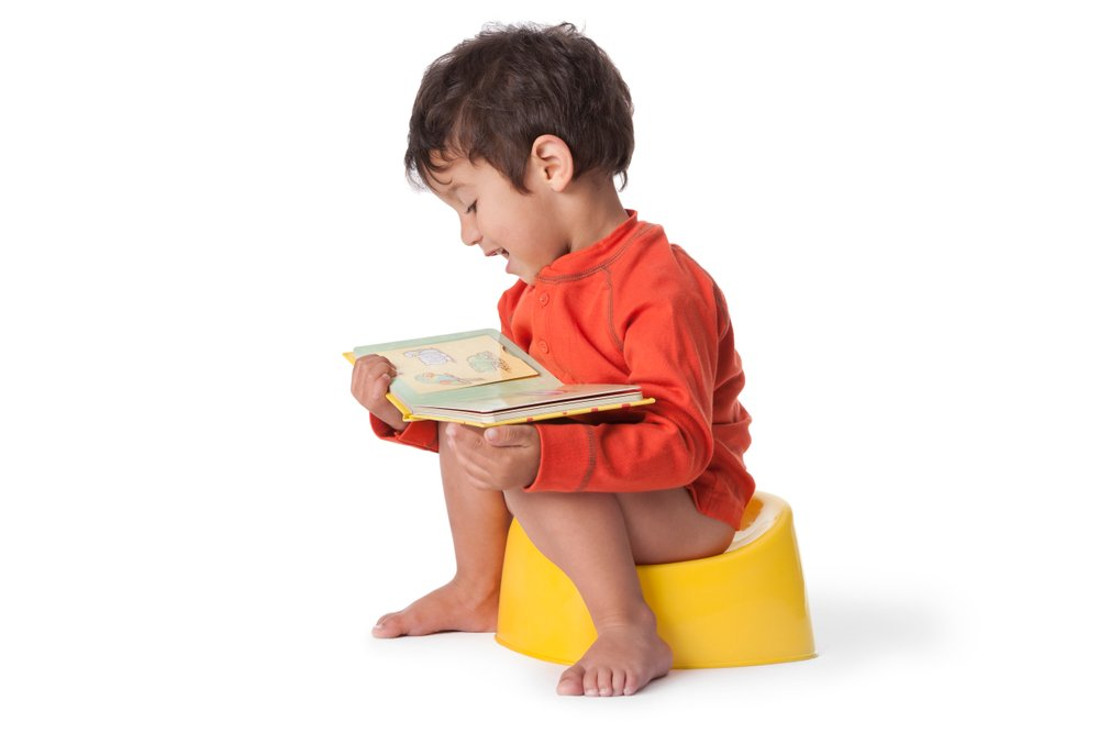A toddler boy sitting on a potty and reading a book. | Photo: Shutterstock