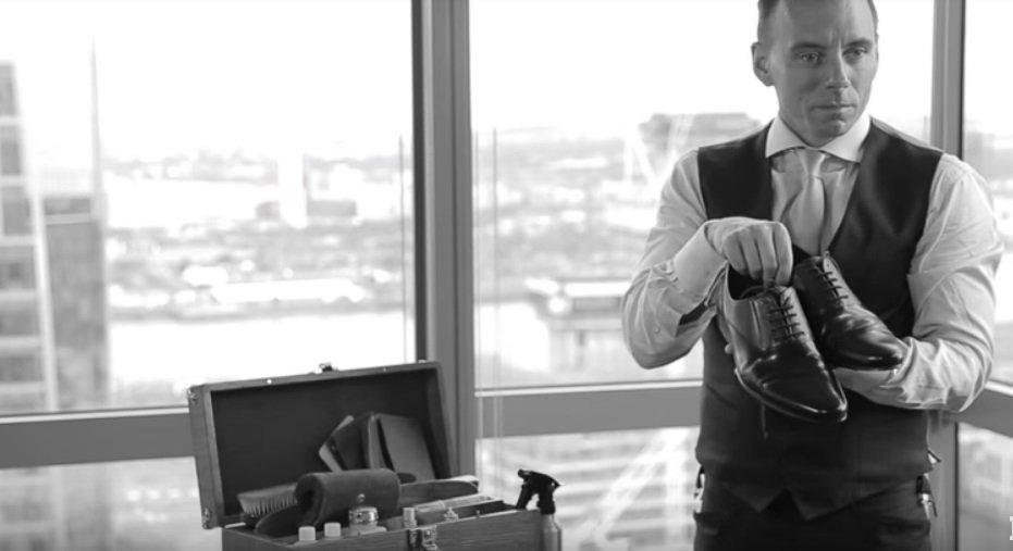 Drew Goodall muestra zapatos que acaba de lustrar en su oficina   Foto: YouTube/IBTimes UK