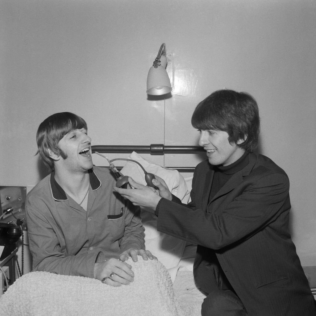 Ringo Starr gets a visit from fellow Beatle George Harrison (1943 - 2001) whilst recuperating from an operation to remove his tonsils  | Getty Images / Global Images Ukraine