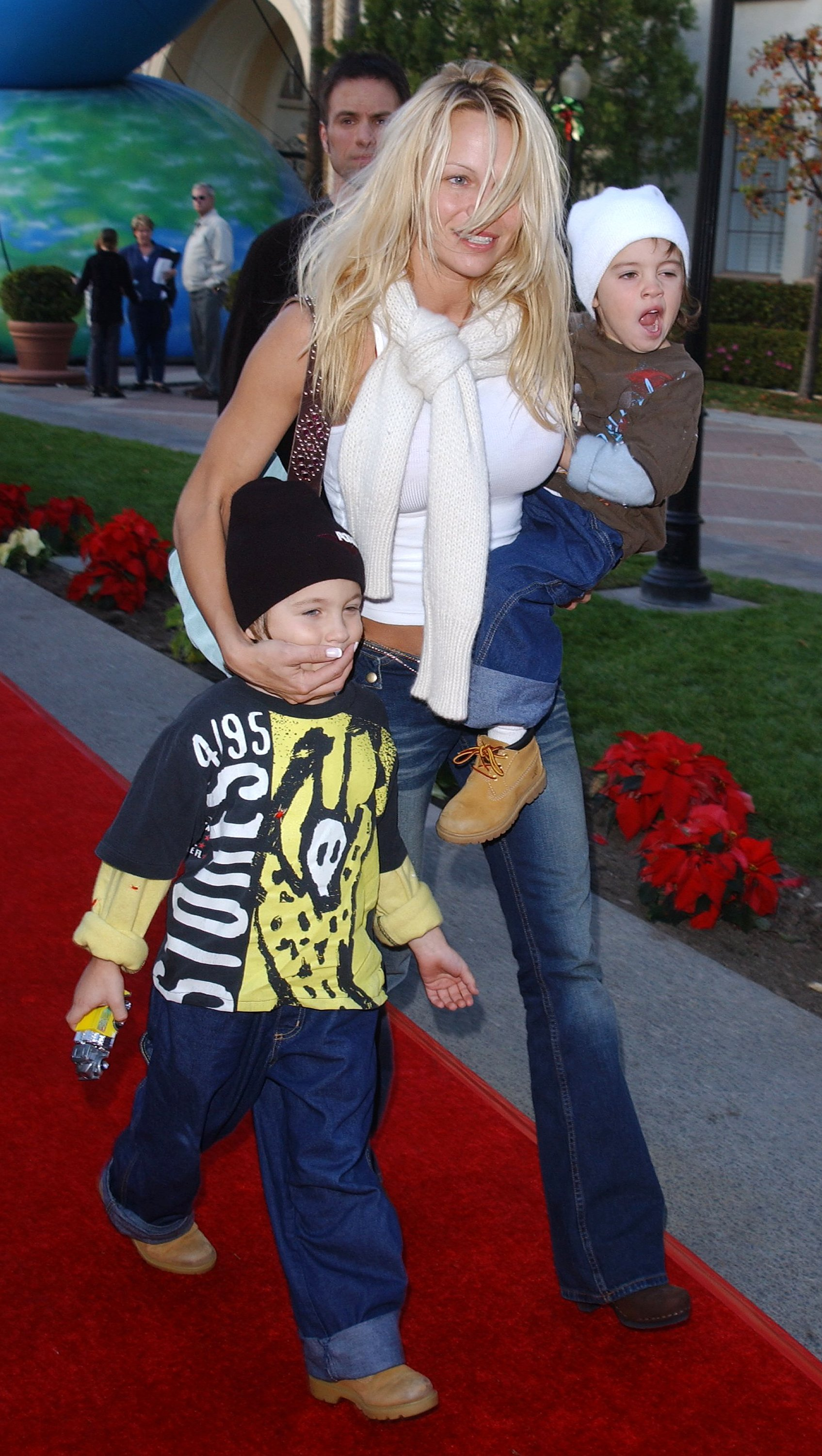 Pamela Anderson walking the red carpet with sons Dylan and Brandon at the Premiere of Jimmy Neutron on December 9, 2001 in Hollywood, CA. | Photo by Vince Bucci/Getty Images