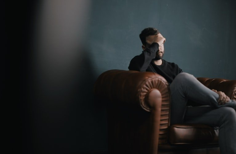 A man seats on a couch with his hand on his face while in deep thoughts | Photo: Unsplash