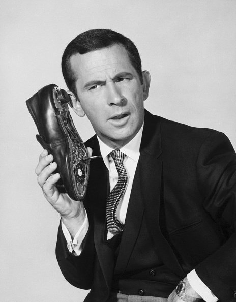 "Don Adams, as secret agent ""86"" Maxwell Smart, talks into his trusty shoe-phone, undated picture. 