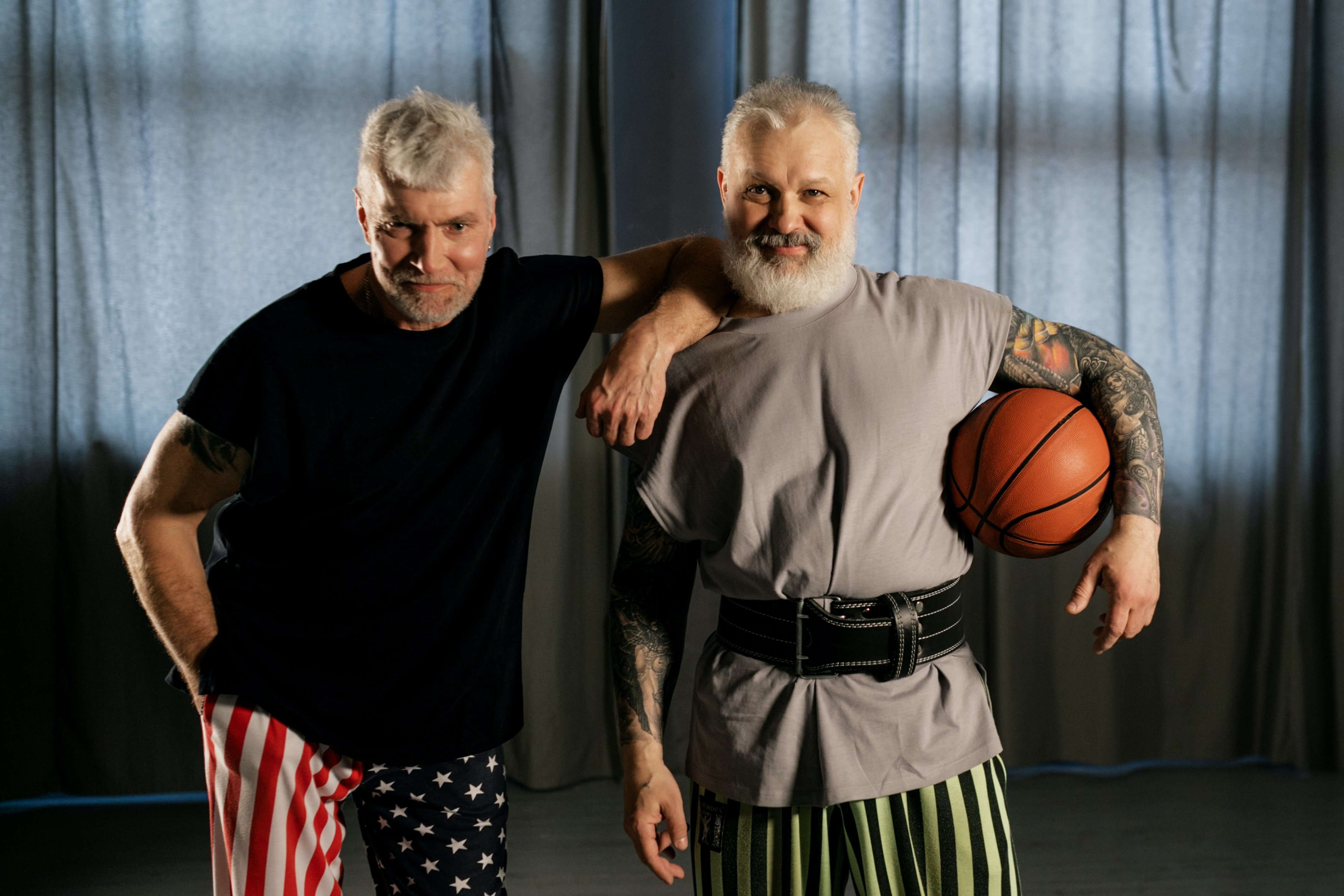 Pictured - Two elderly men smiling while one holds a basketball ball | Source: Pexels