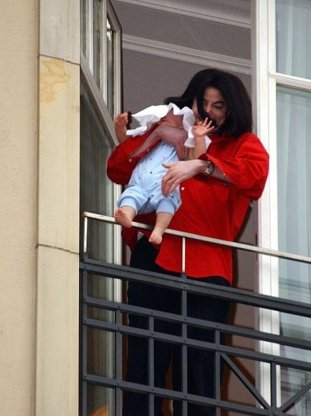 Michael Jackson holds his son eight-month-old son Prince Michael II over the balcony of the Adlon Hotel November 19, 2002, in Berlin, Germany. | Source: Getty Images.