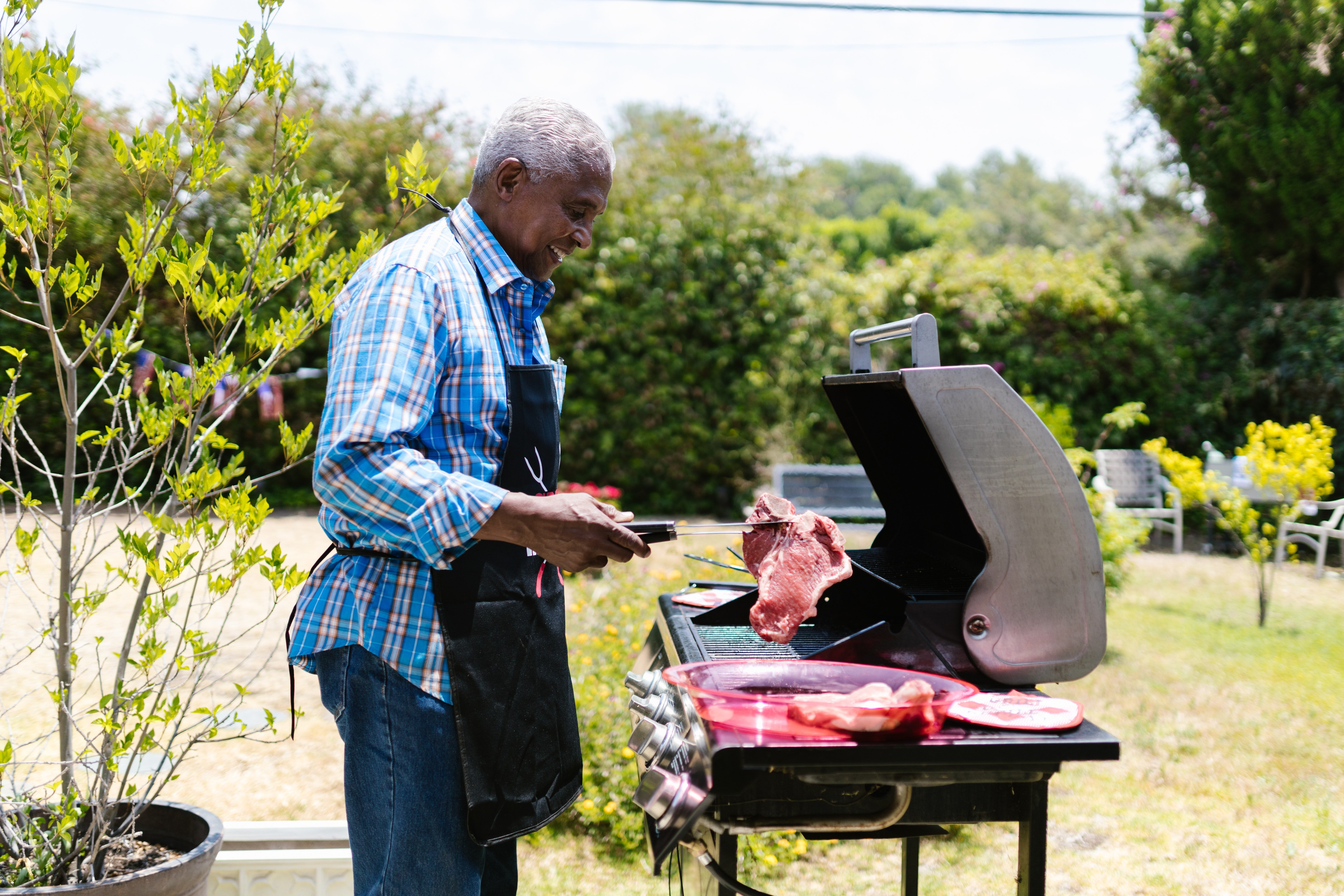 A happy man grilling meat | Photo: Pexels
