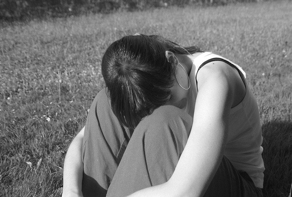 Verzweifelte Frau sitzt im Gras | Quelle: Pixabay