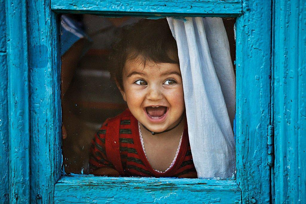 Enfant souriant à travers la fenêtre | Getty Images