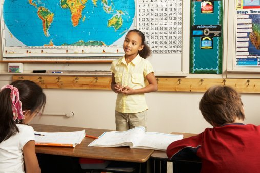 Photo of a young girl standing and talking in front of classroom to other children | Photo: Getty Images