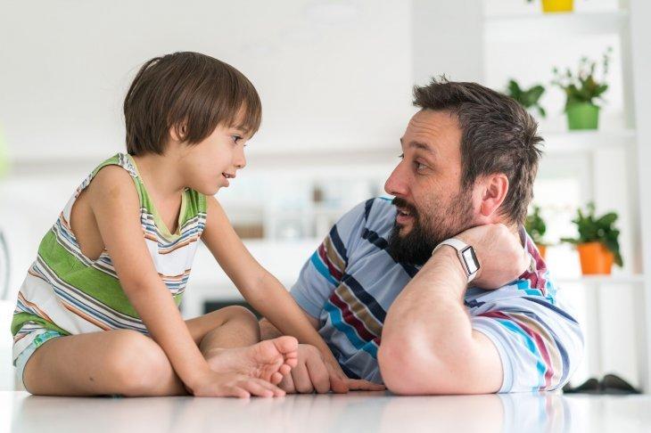 Un enfant qui discute avec son père | Photo : Shutterstock