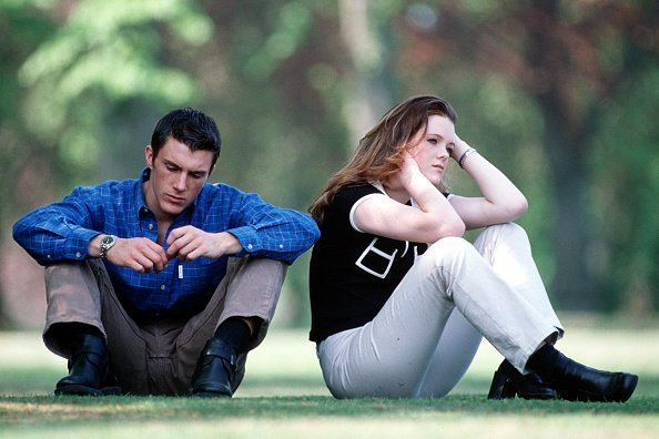 A young couple in casual dress sitting in the park, the woman appears upset and has back turned on the man | Photo: Getty Images