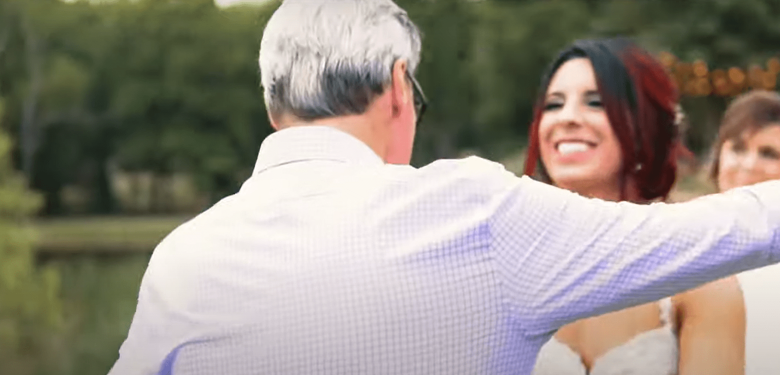 A father and daughter going in for a hug. | Source: youtube.com/Megan Roy
