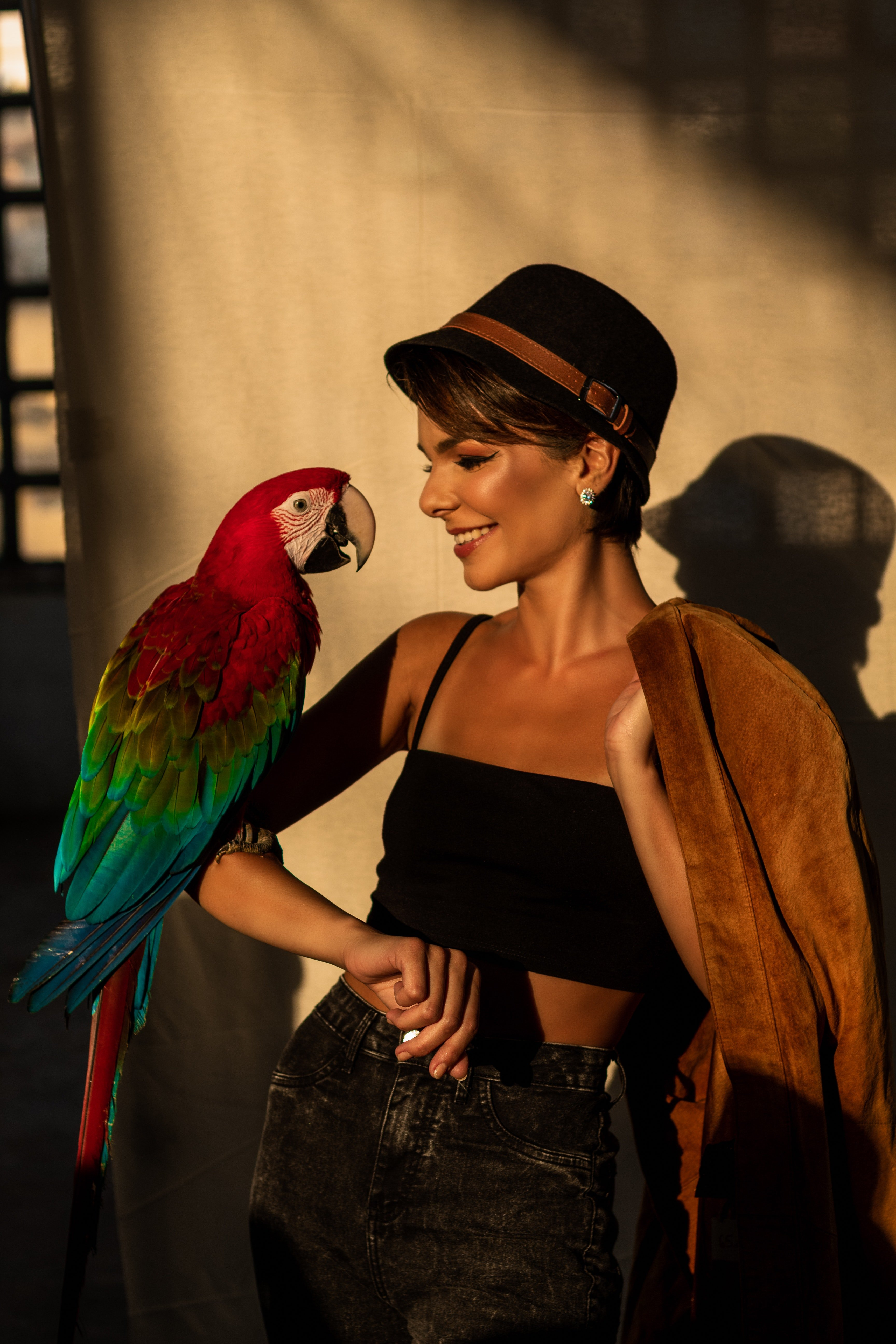A big colorful parrot sitting on the arm of a woman wearing a hat.   Photo: Pexels/ Luiz Fernando