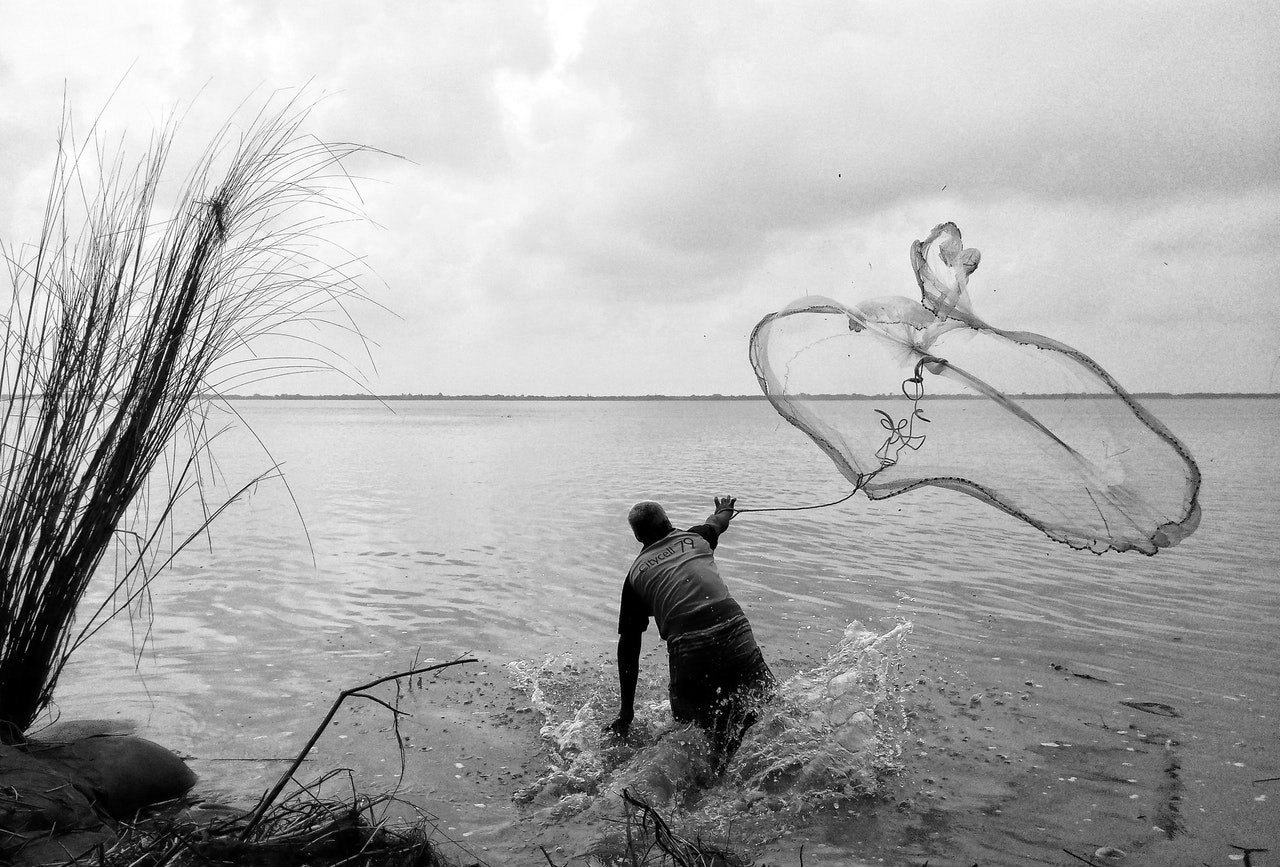 Photo of a man casting his fishing net to the sea | Photo: Pexels