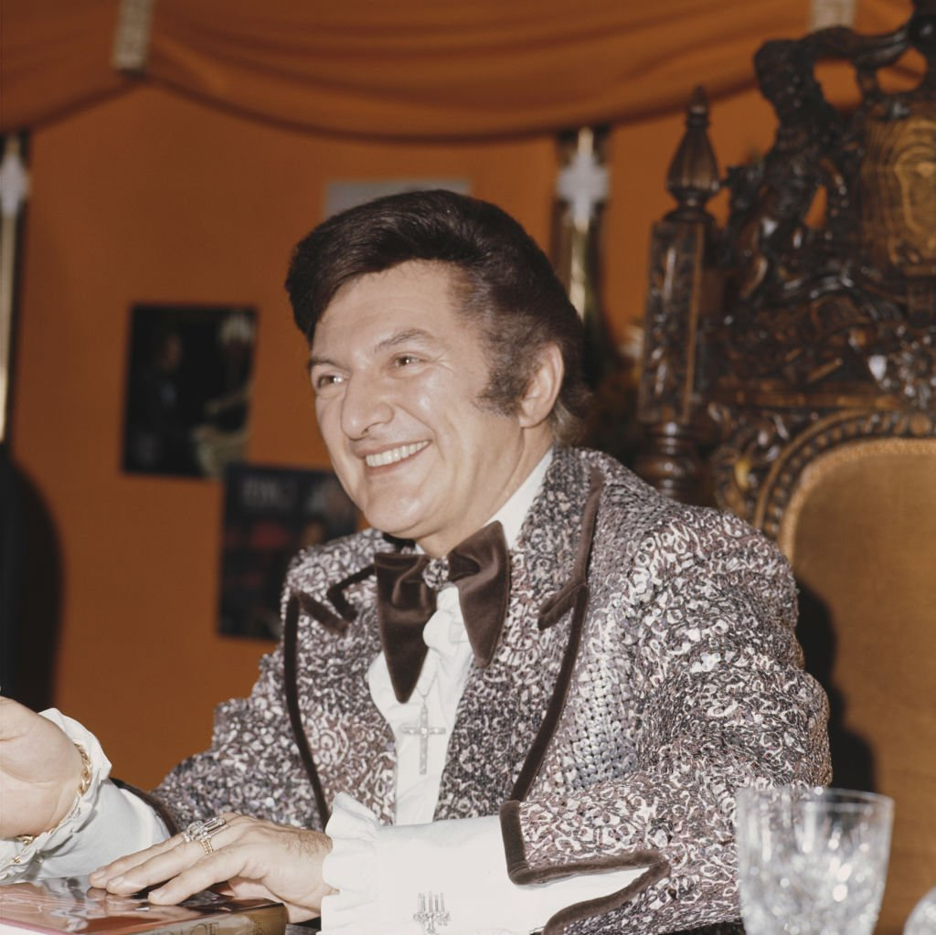pianist and singer Liberace (1919 - 1987) signs copies of his book in Selfridges, London | Getty Images