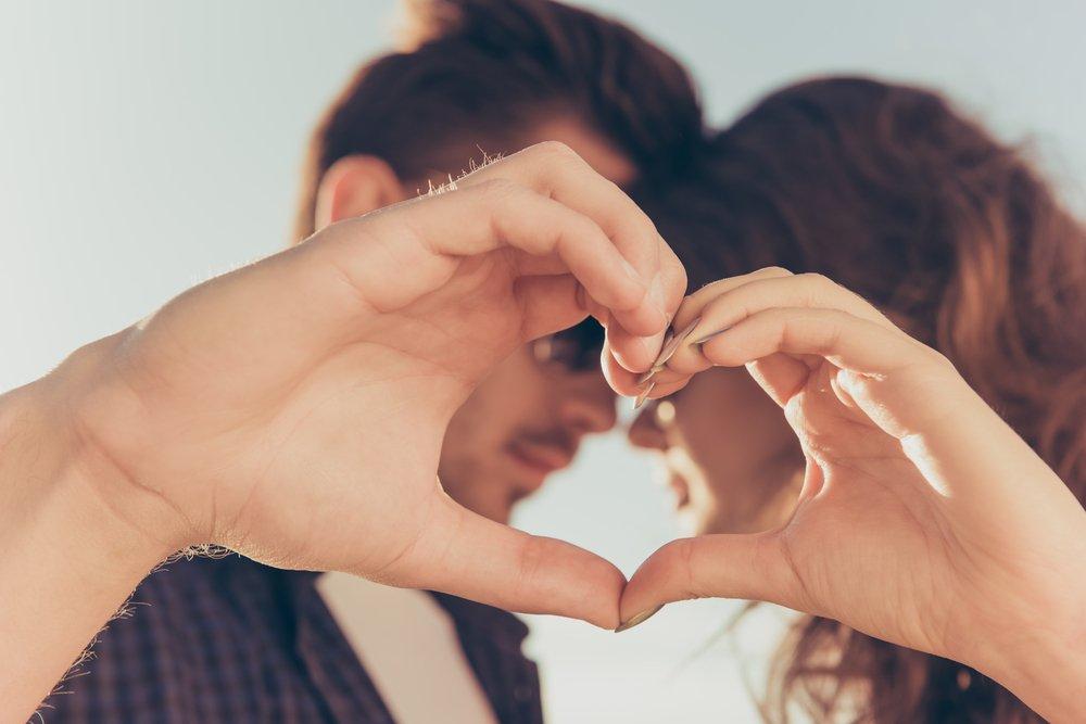 Pareja formando un corazón con las manos.  Fuente: Shutterstock
