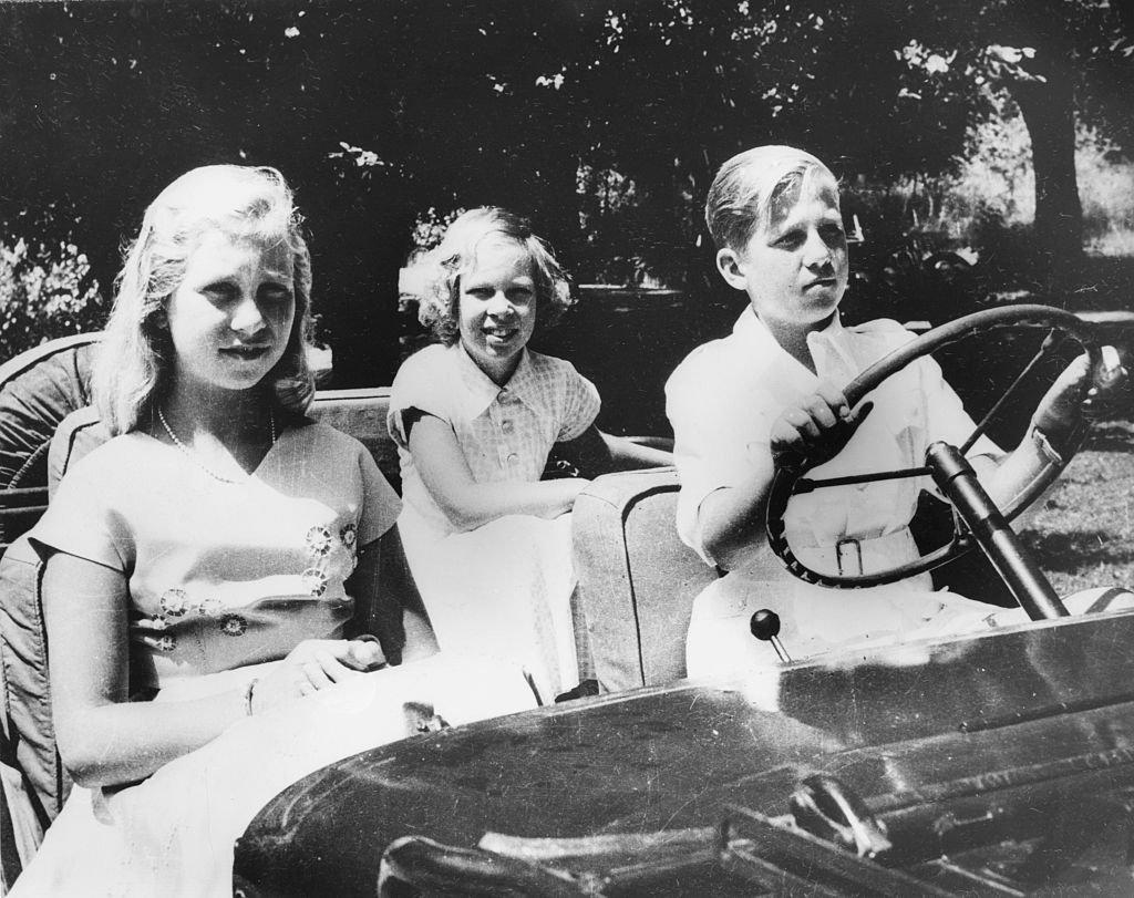 El rey Consorte Constantino de Grecia conduciendo con sus hermanas, las princesas Irene y Sofía, cuando todos eran niños, 1955. | Foto: Getty Images